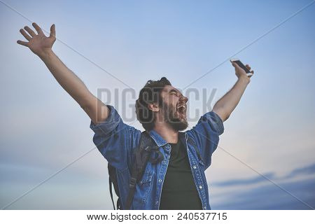 I Am Free. Excited Young Man Is Enjoying The Nature During His Journey. He Is Raising Hands Up And S