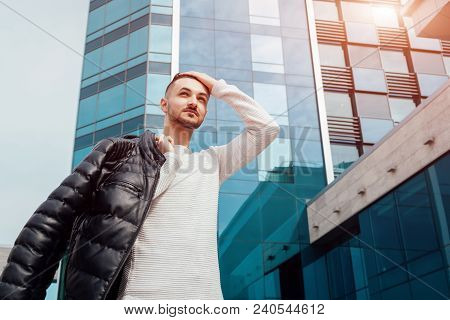Arabian Man Holding His Coat And Walking In City Center. Young Man Puts Coat On Shoulder. Stylish Ha