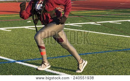 A High School Girl Is Pulling A Sled With Weights On It During Winter Track And Field Practice On Gr