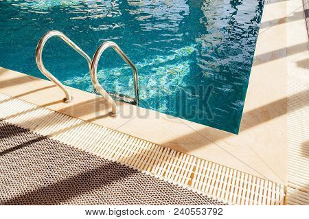 Grab Bars Ladder In The Blue Swimming Pool.