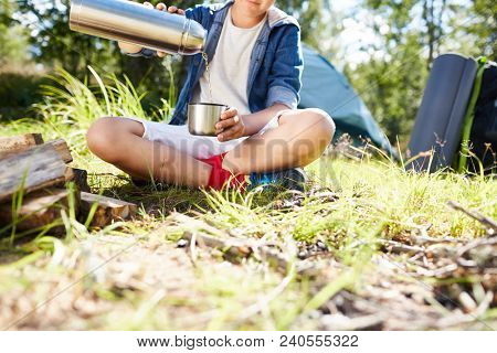 Young tripper pouring hot water from thermos into his mug while sitting by campfire on grass