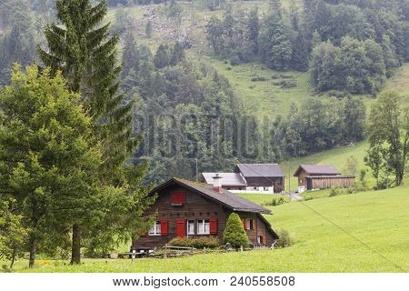 Alpine Mountain Landscape -  Green Meadow Against The Mountain . Alpine Village. Swiss Alps At Summe