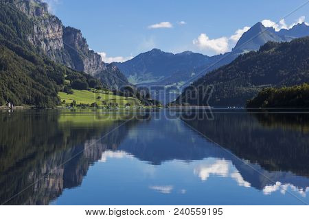 Mountain Lake Klontalersee  On Background Of Majestic Mountains Reflected In The Water And Bright Cl