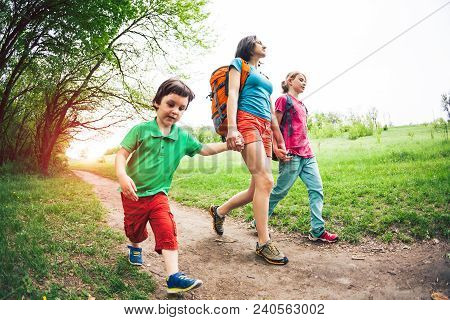 A Woman With Children Goes Hiking. The Woman Took Her Sons By The Arms. The Family Goes On A Dirt Ro