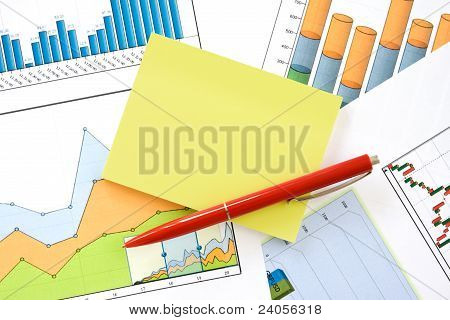 Pen And Memo Over Charts