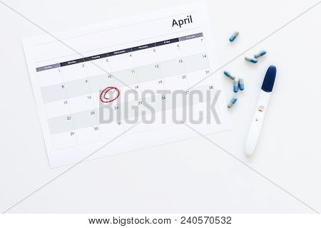 Planning Pregnancy. Positive Pregnancy Test Near Calendar Page And Pills On White Background Top Vie