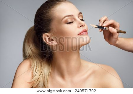 Beautiful Woman Applying Liquid Foundation On Her Face On Grey Background