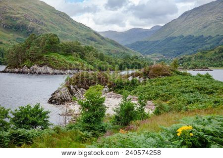 Loch Shiel shore, a National Scenic Area in Lochaber, Highland, Scotland, UK, with  Glenfinnan Viaduct and monument in background