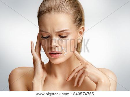 Upset Woman Touching Her Face. Photo Of Attractive Woman With Anti Aging Cream On Grey Background. B