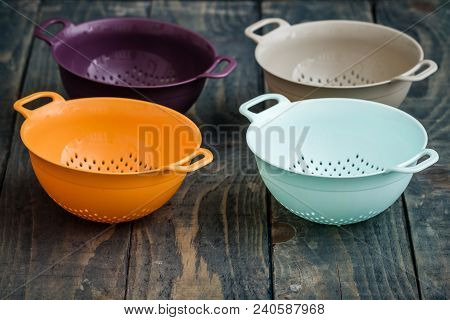 Colorful Plastic Colanders With Handles On Blue Wooden Background