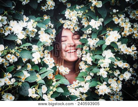 Happy Young Smilling Girl Having Fun Catches Petals With His Hands On Background Of Blooming Bush Wi