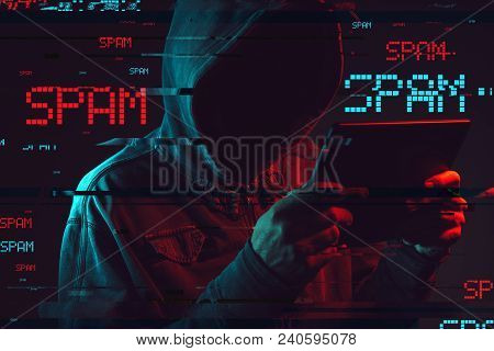 Electronic Spamming  Concept With Faceless Hooded Male Person Using Tablet Computer, Low Key Red And