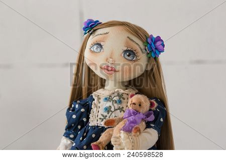 Portrait Of Textile Handmade Vintage Doll With Blue Eyes, Long Brown Hair In Old Blue Textile Dress