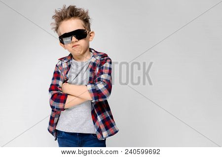 A Handsome Boy In A Plaid Shirt, Gray Shirt And Jeans Stands On A Gray Background. The Boy In The Bl