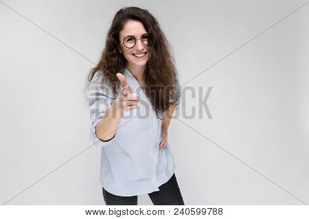 Young Girl With Glasses On A Gray Background. Portrait Of A Young Beautiful Girl. A Charming Girl In