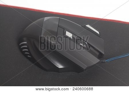 Computer Modern Gaming Mouse On Black Mouse Pad Isolated On A White Background