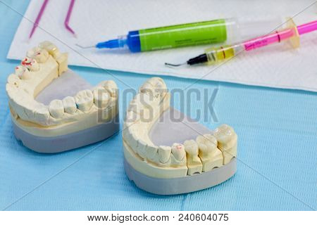 Close-up upper and lower artificial jaws with colour marks in dentist office, dental instruments, gel and glue.