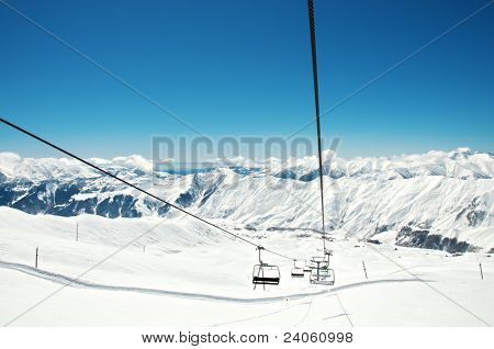 Ski lift chairs on bright winter day poster