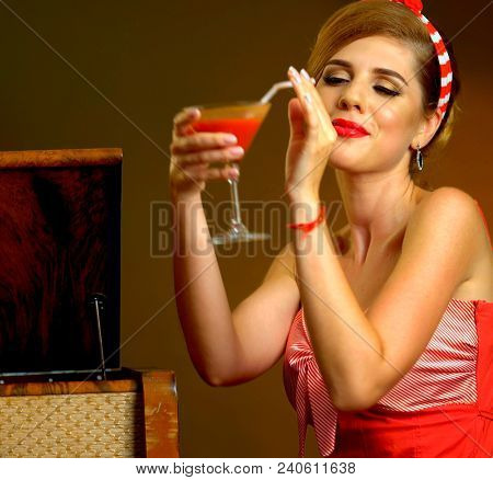 Kiss blow of pin up girl drink bloody Mary cocktail. Pin-up retro female style. Girl pin-up style wearing red dress and wind blowing. Delightful collection in retro style.