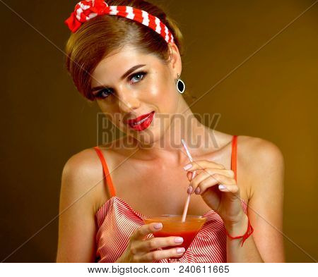 Pin up girl drink bloody Mary cocktail. Pin-up retro female style. Girl wearing red dress seduces men. Girl of your dreams.