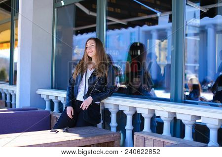 Young Female Person Resting Near Window Of Street Cafe And Sofa. Concept Of Resting Outside.
