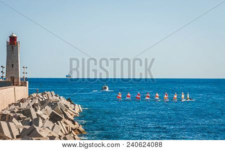 Nice, France - October 13, 2009: Group Of Yachtsmen With Red And White Sails Passing By Lighthouse I