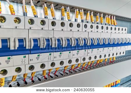 Range of electrical modular circuit breakers in electrical Cabinet. Neat and high-tech Assembly of switchboards. The wires or cables are connected to the switches and laid in the cable channels. poster