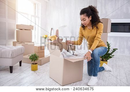 New Beginning. Charming Curly-haired Girl Packing A White Lamp Into The Box While Packing Her Belong