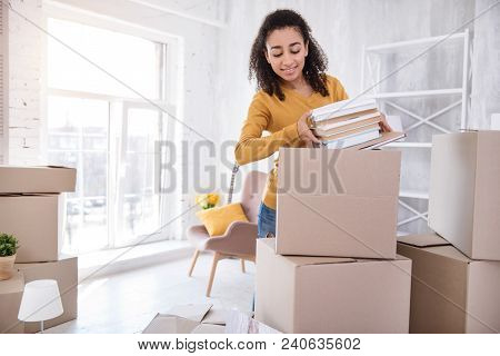 Favorite Books. Pleasant Curly-haired Girl Packing A Pile Of Books Into A Big Box Before Moving Out