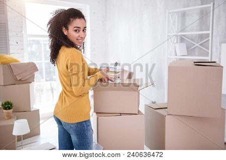 Upbeat Mood. Beautiful Young Girl Smiling At The Camera While Unpacking Her Belongings And Taking A