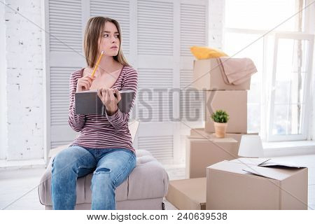 Neat And Organized. Pleasant Young Woman Sitting On The Pouf In Her Old Apartment And Checking The L