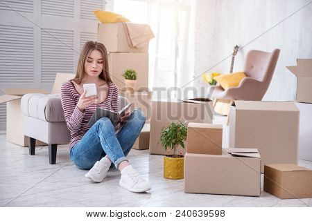 Need Assistance. Charming Young Woman Sitting On The Floor And Checking The Number Of Removers Compa