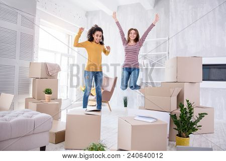 Happy To Move In. Upbeat Young Girls Jumping Happily In The Living Room Of Their New Apartment Befor
