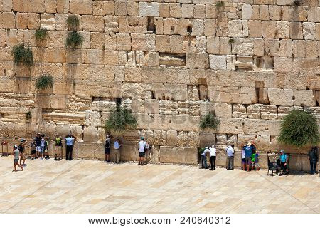 JERUSALEM, ISRAEL - JULY 04, 2016: People praying at Western Wall - ancient wall in Old City of Jerusalem, originally was part of the Second Jewish Temple now is the holiest place in Judaism.