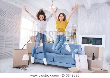 Upsurge Of Emotions. Pleasant Cheerful Girls Jumping Happily In A New Apartment While Celebrating Mo