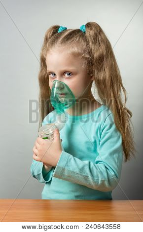 Mesh Nebulizer With Child Mask In Hands Of Sick Child, On Grey Background