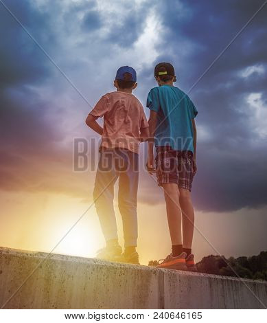 Two Boys Brothers Watching Sunset Under Stormy Sky