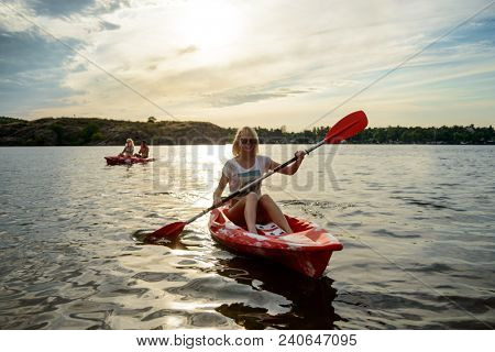 Young Happy Woman Paddling Kayaks on the Beautiful River or Lake under the Dramatic Evening Sky at Sunset