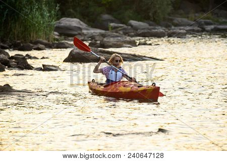 Young Woman Paddling Kayak on the Beautiful River or Lake among Stones at the Evening