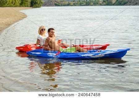 Young Happy Couple Resting in Kayaks on the Beautiful River or Lake Beach at the Evening
