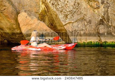 Young Woman Paddling Red Kayak on the Beautiful River or Lake under High Rock in the Evening