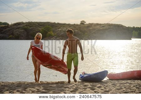 Young Happy Couple Carrying out Kayak to the Sand Beach from the Water on the Beautiful River or Lake at the Evening