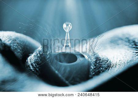 Macro closeup on human eye with liquid drop