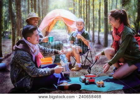 Young Asian People Enjoy Camping In Forest,eating Food Outside Tent,hiking,teamwork Concept.
