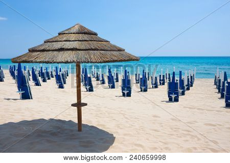 Straw Umbrella With Background Blue Sea, Sky And Sand Beach. Nobody, Outdoor. Italy, Puglia