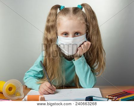 Sick Child In Protective Bandage Draws Sitting At Table, Next To An Inhaler And Mask