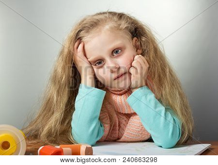 Sad Sick Girl In Warm Scarf Sitting At Table, Next To Inhaler And Mask