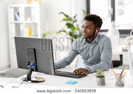 business, technology and people concept - happy african american businessman with earphones and computer computer listening to music at office