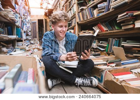 Positive Young Man Sitting On The Floor In A Cozy Public Library, Reading Books And Smiling. A Young