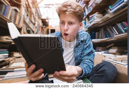 Amazed Young Man Reads A Book In A Public Library. A Student Sitting On The Floor In A Public Librar